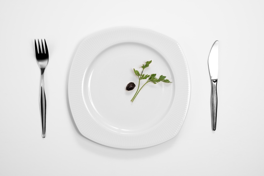 Single black olive and parsley on the middle of a plate, knife and fork.