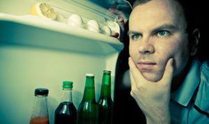 man looking in refrigerator