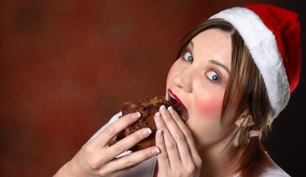 Santa girl with red cheeks eating a piece of chocolate cake