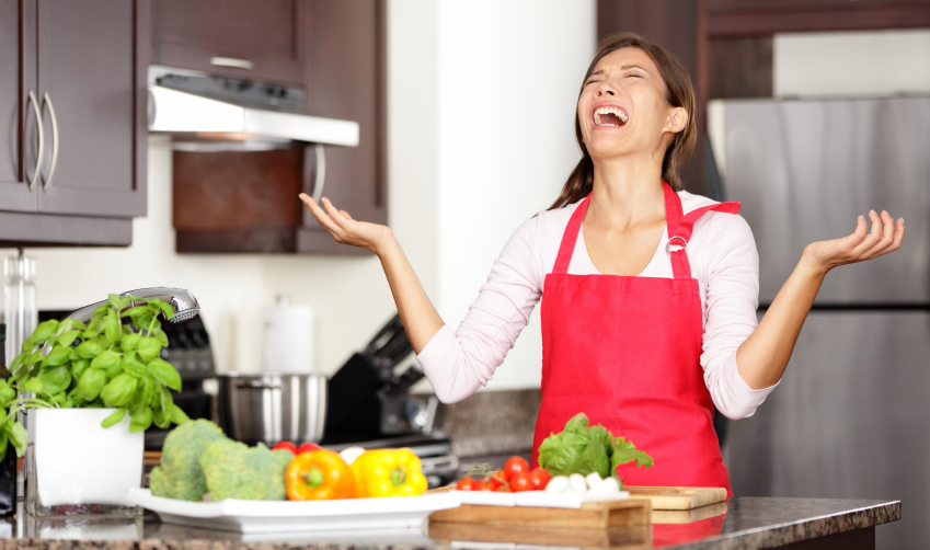 Funny cooking image of woman crying and screaming in kitchen giving up making food after unsuccessful cooking attempt. Beautiful young mixed-race Asian Chinese / Caucasian woman in kitchen.