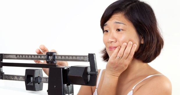 Cute middle age woman on vertical weight scale looking disappointed at her current weight