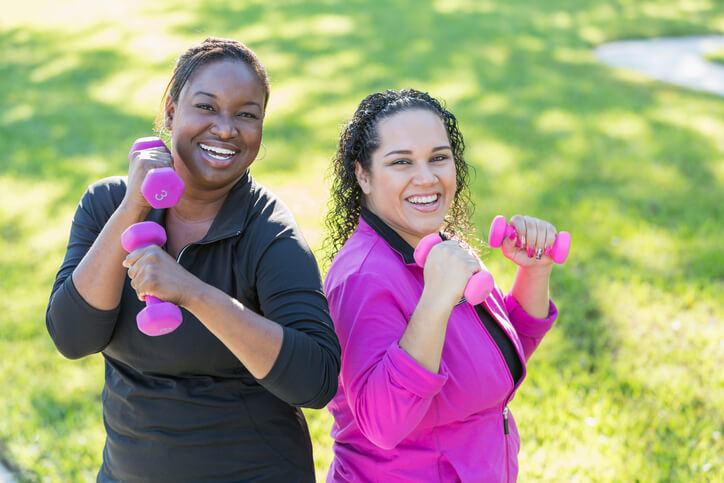 Two multi-ethnic women in their 30s exercising outdoors on a sunny day, lifting handweights. They are standing, smiling and looking at the camera.