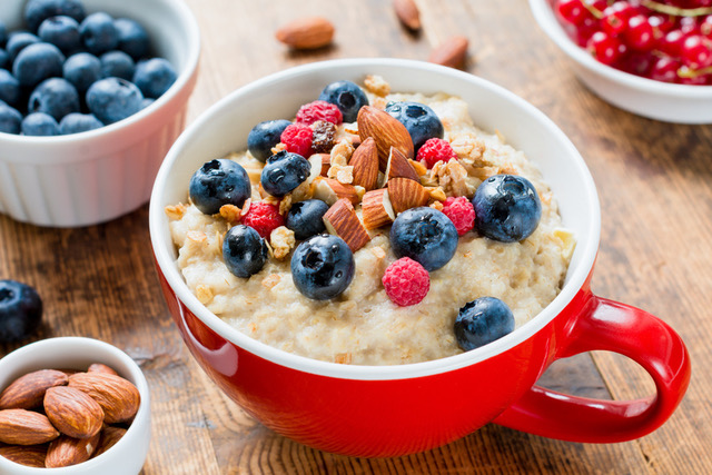 Close up view of delicious breakfast oatmeal porridge in red bowl topped with fresh blueberries, raspberries, almonds and granola.